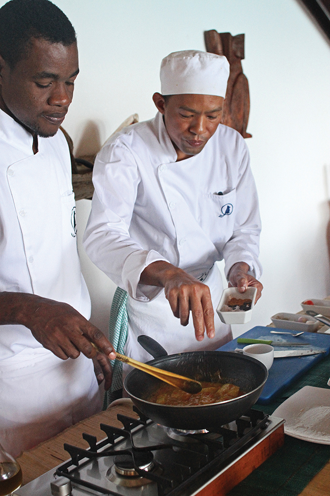 Chefs Claude Raherivelo and Fidele preparing Malagasy fish curry in the resort's kitchen.
