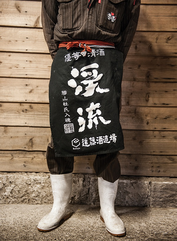 A brewery worker showing off his maekake (apron) at Endo Shuzo in the mountainous Nagano area.