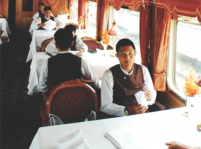 Staff prepping for dinnertime service in one of the E&O's wood-paneled dining cars.