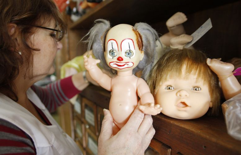 """One of the """"doctors"""" of the Hospital de Bonecas, reviewing a doll that is to be repaired."""