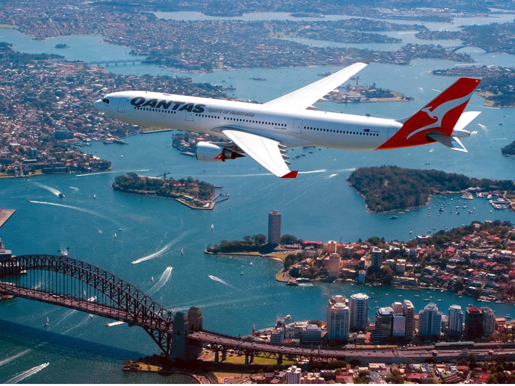 A Qantas A330 soars over Sydney's harbor.