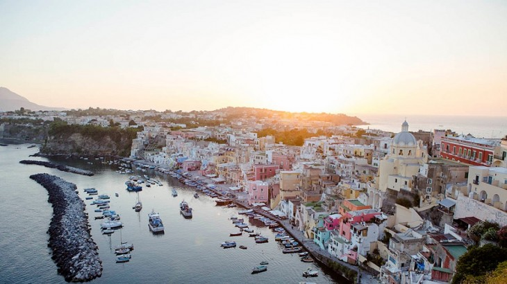 The sun sets over an Italian harbor.