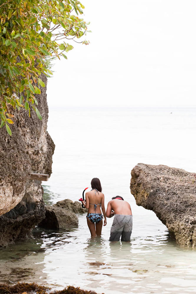 A couple braves the rocks for some snorkeling off Panglao Island.