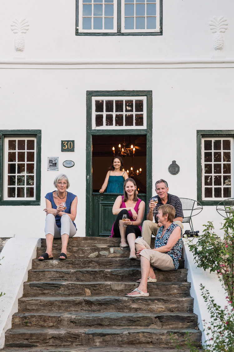 A family enjoying a couple of glasses of wine on the steps of their Cape Dutch row house on historic Church Street in Tulbagh.