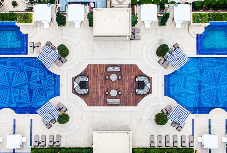 A bird's eye view of the hotel's outdoor swimming pool area.