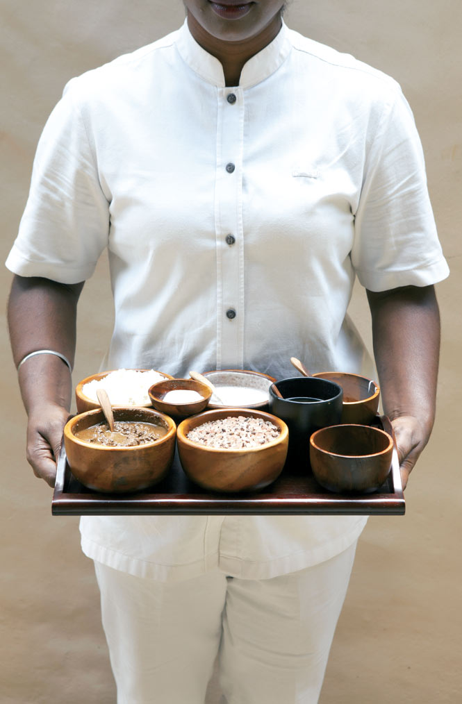 At The Banjaran Hotspings Retreat near Ipoh, a therapist displays the ingredients used in the spa's Adam Traditional Malay Journey ritual, including a boreh scrub, rock salt, coconut-milk powder, and a blend of lavender and lemongrass oils.