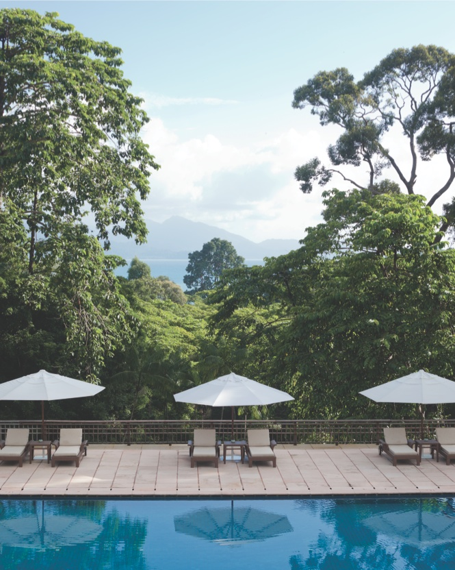 The pool terrace at The Datai looks out across forest and sea.