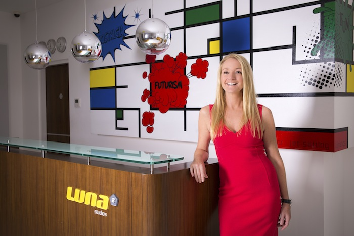 Melanie Hall in the lobby of Luna2 Studios with her own design dubbed Nostalgia, Futurism & Fun, painted by Irene Hoff.
