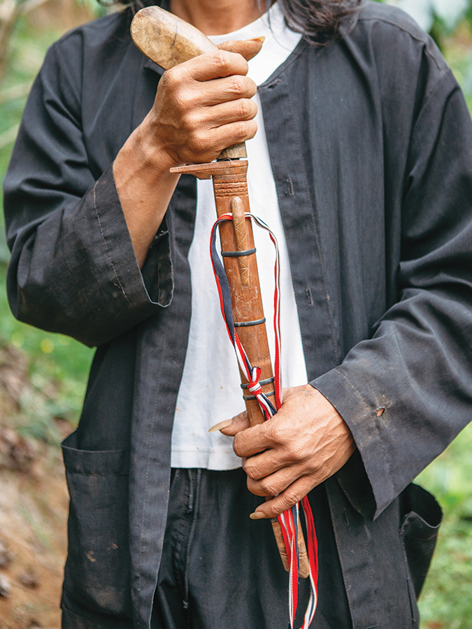 Malabar Mountain's farm manager, Camat, shows off one of the tools of his trade, a parang, or machete.