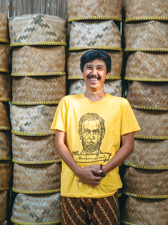 Klasik Beans' founder Eko Purnomowidi flashes a smile in front of woven bamboo baskets used for collecting coffee cherries.