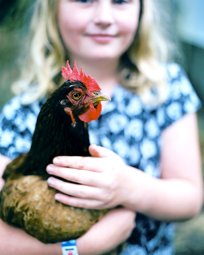 A Greymouth girl showing off her pet rooster.