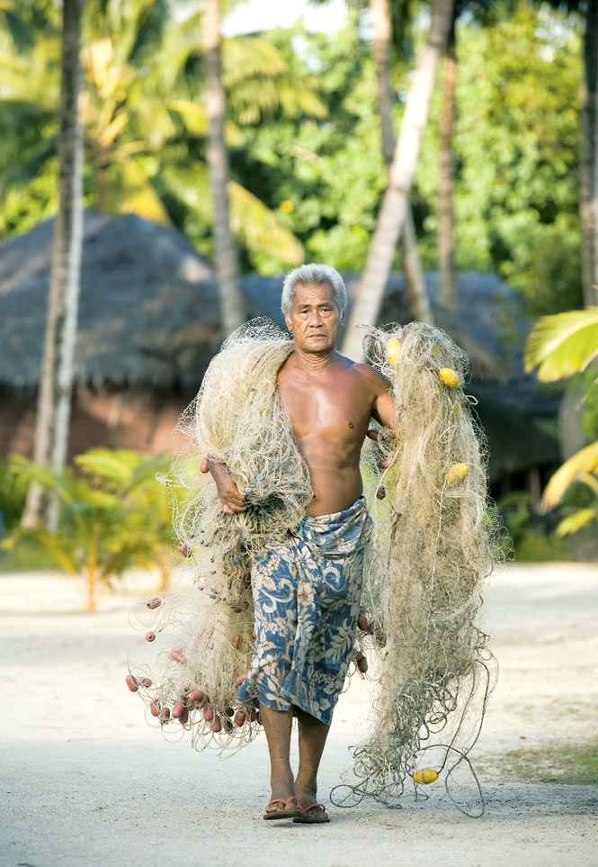 A fisherman readying his nets for a night on the water.