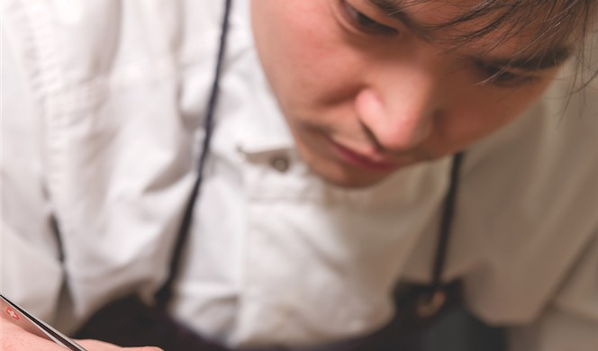 FiftyThree chef Michael Han putting the final touches on one of his signature creations: glazed new potatoes with duckweed, wild garlic flowers, Parmesan emulsion, and a