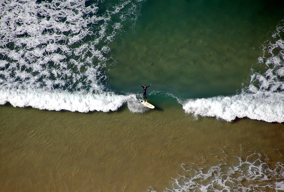 Bird's eye view of a surfer catching the waves.