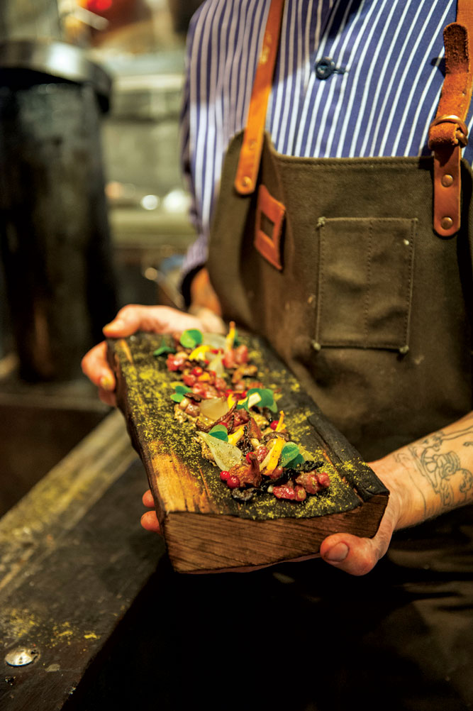 The fire pit in the 'stone age' kitchen at Stockholm's Ekstedt produces remarkable dishes like this smoked beef tartare with black trumpet mushrooms, chanterelles, and lingonberrie.