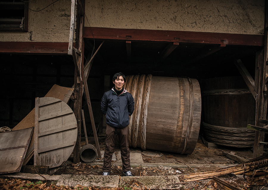 A kurabito (brewery worker) standing in front of obsolete equipment at Tomita Shuzou, a 15th-generation sake brewery located deep in the countryside of Shiga prefecture, western Japan.