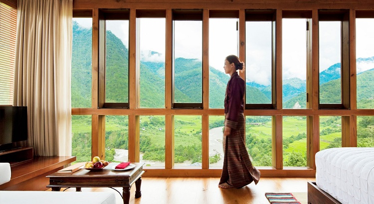 Smiling staff in traditional Bhutanese dress and views of densely forested hills unfold as you enter the property.