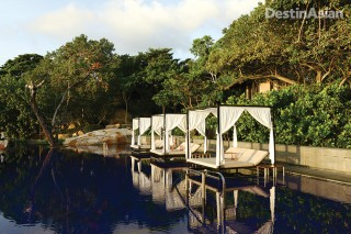 Canopied daybeds flank the swimming pool at Vana Belle.