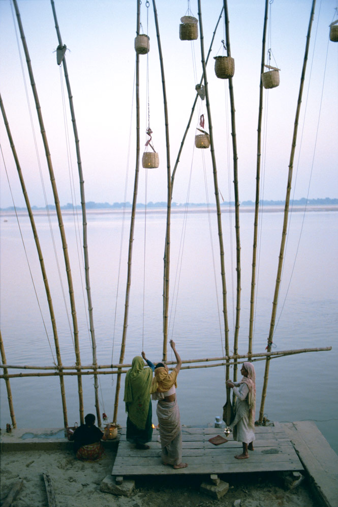 Raising lanterns above the banks of the Ganges on the eve of a festival.
