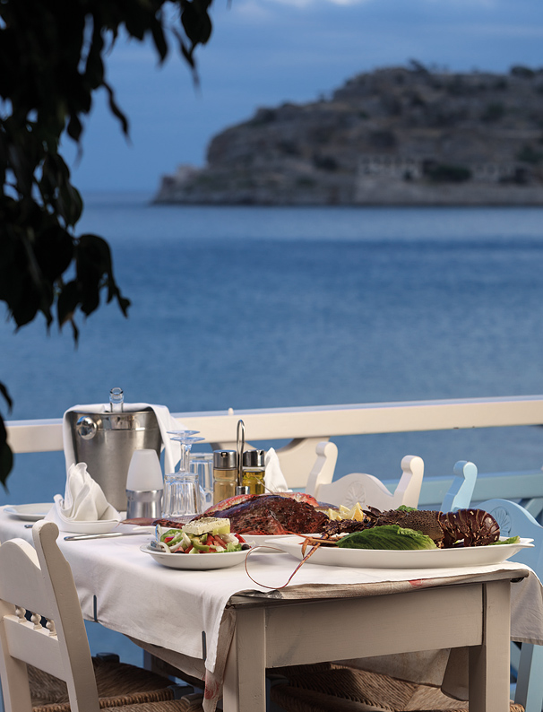 A seafood-laden table at Delphini, where views extend to the former Venetian island fortress of Spinalonga.
