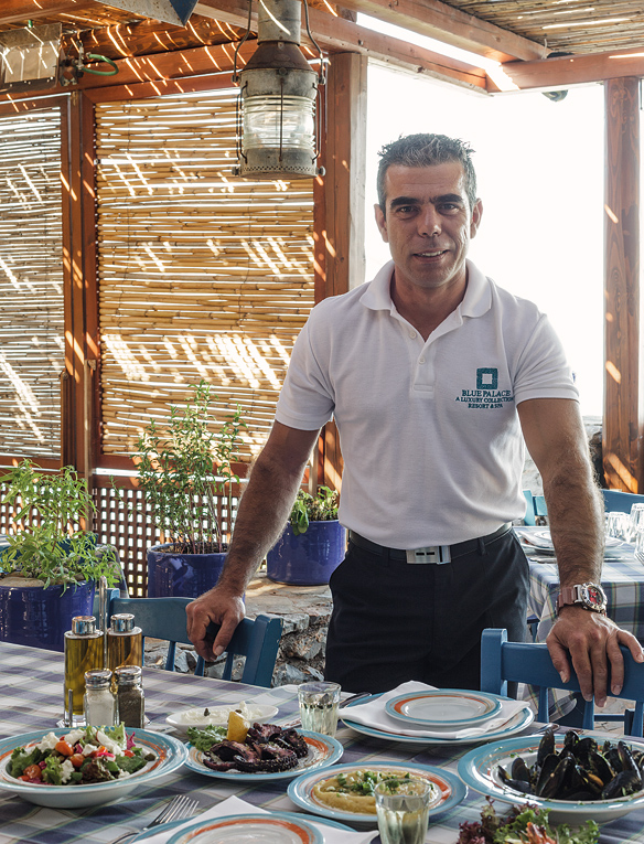 Restaurant manager Haris Alexis at the resort's Blue Door taverna, with a spread of Cretan classics including fava, grilled octopus in red-wine vinegar and olive oil, and steamed mussels.