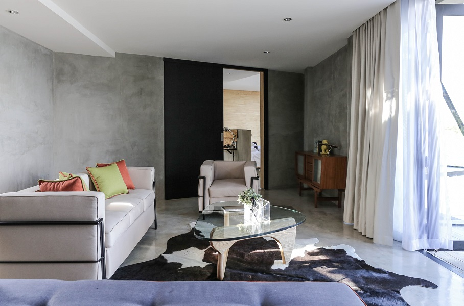 A luxe cabin suite is designed with polished concrete floors and colorful accents.